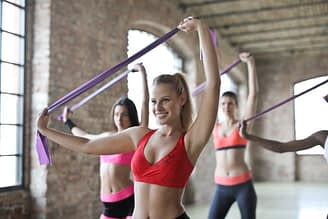 women in sports bra stretching in the gym with a piece of cloth